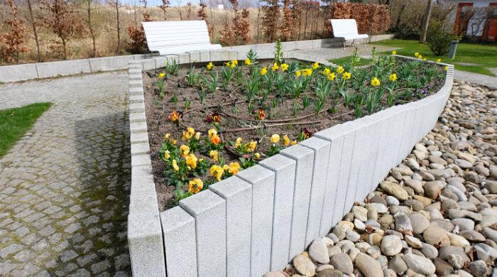 Parkanlage mit Bänken und gepflasterten Wegen und Blumenrabatte in Frühlingsbepflanzung