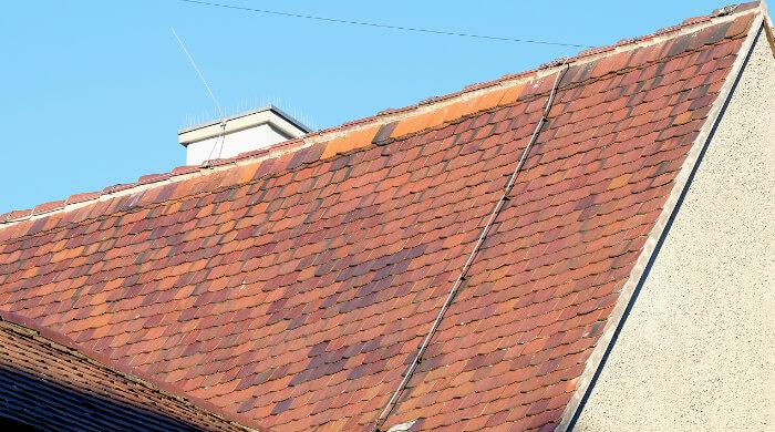 Blitzableiterdraht auf einer Dachfläche und Fanganlage am Schornstein