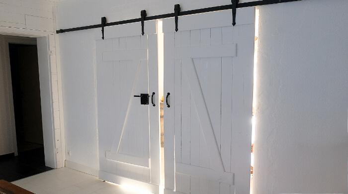 Innetür als Schiebetür vor der Wand laufend mit offen sichtbarer Laufschiene und hängender Konstruktion