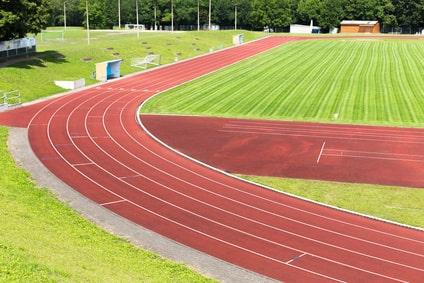 Eingefasste Rasenkanten zwischen Spielfläche und Laufbahn bzw. Sprungbereich auf einem Sportplatz