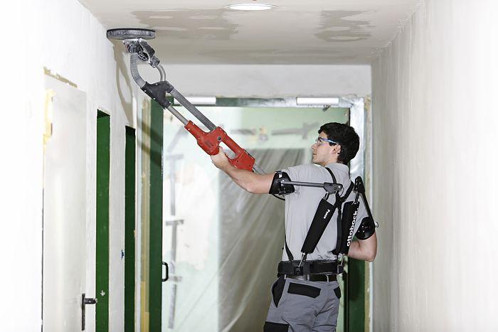 Arbeiter mit Exoskelett beim Teleskopschleifen