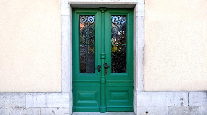 Historische Holztür als Hauseingangstür mit Glaseinsätzen und schmiedeisernen Verzierungen