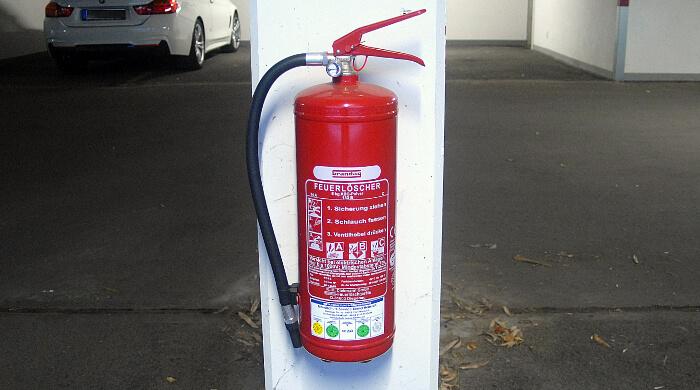 ABC-Pulver-Feuerlöscher mit Prüfvermerken angebracht an einem Pfeiler in einer Tiefgarage