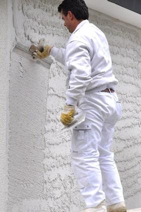 Verputzen einer Fassade mit Spritzputz