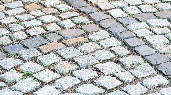 Ungebundenes Mosaikpflaster aus Granitpflaster- und Basaltpflastersteinen, dass zur Markierung von Parkflächen genutzt wird