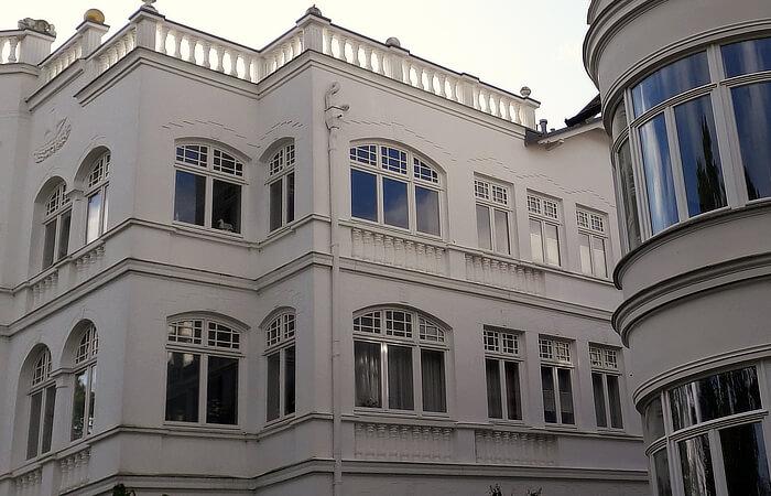 Zwischen Fenstergesims und Stockwerkgesims eingefasste Halbsäulen-Bänder unter den Fenstern