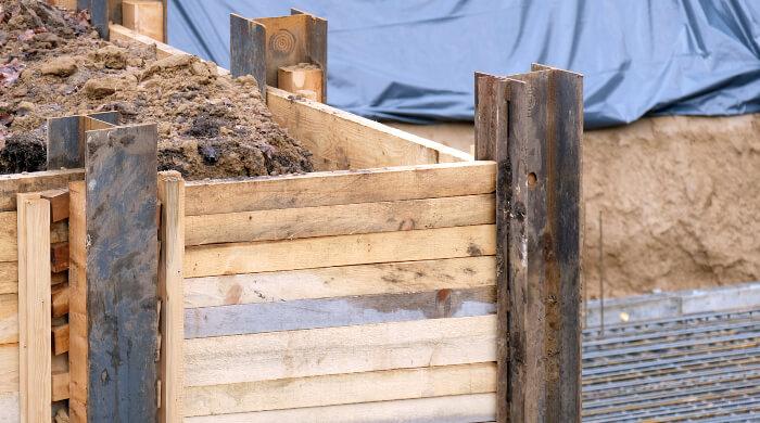 Verbau an einer Baugrube aus DoppelT-Trägern und Holzbrettern
