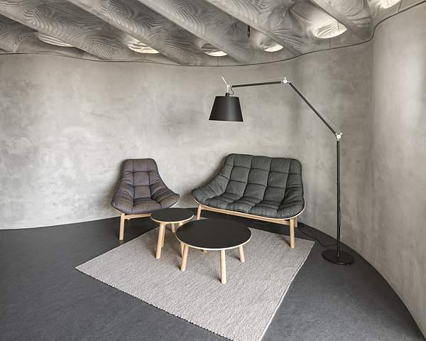 Sitzgruppe im DFAB HOUSE unter filigraner Betondecke, die in 3D-gedruckten Schalungen gegossen wurde.