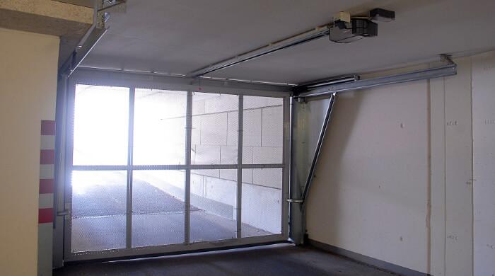 Garagentor aus Metallgitter, das beim Öffnen unter die Decke geschoben wird.