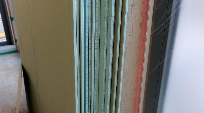 Imprägnierte und eingefärbte Gips-Wandbauplatte zur Verwendung in Feuchträumen